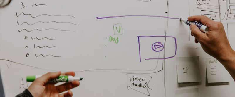 Photo d'un tableau effaçable sur lequel des schémas ont été dessinés, on voit deux mains de personnes différentes tenant des stylos