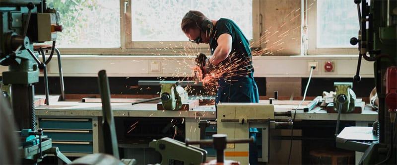 Image d'un homme dans un atelier en train de découper du métal avec une scie circulaire