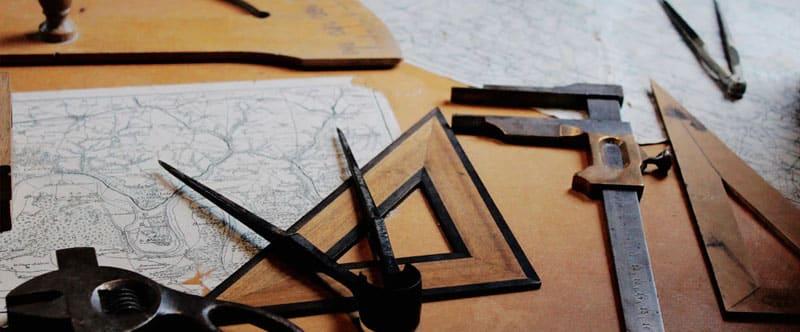 Photographie d'outils qui semblent destinés à la cartographie, équerre, compas, rapporteur, posé sur des cartes.