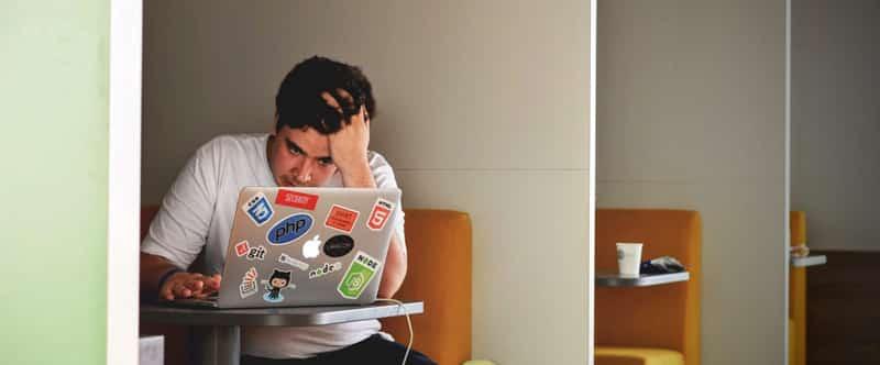 Image d'un jeune homme qui semble en difficulté devant son ordinateur portable, assis dans ce qui semble être un diner.