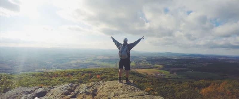 Photo d'un homme avec un sac à dos, de dos, en haut d'une colline qui lève les bras au ciel. Se retrouver premier sur google, sah quel plaisir.