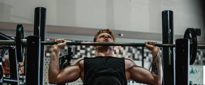 Image d'un homme musculeux à la salle de sport en train de soulever une altère sur un banc de pousse.