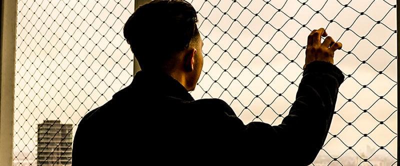 Photo d'un homme de dos qui regarder à travers un grillage, on le devine en haut d'un immeuble à regarder la ville