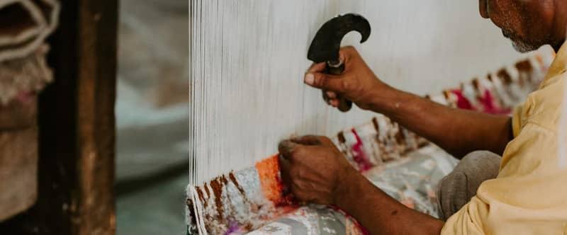 Image où l'on devine un homme tisser à la main un tapis richement décoré.