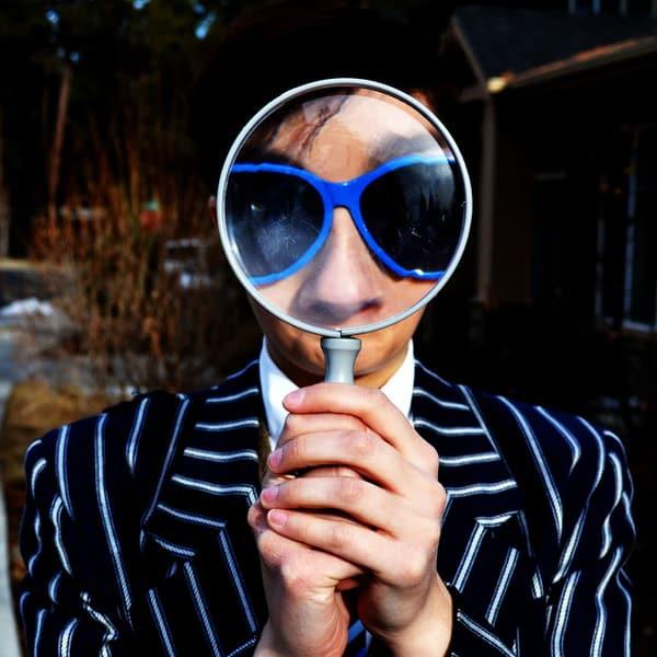 photo d'un homme en costume rayé avec des lunettes bleues, il tient une loupe devant le visage ce qui agrandit ses lunettes et son nez