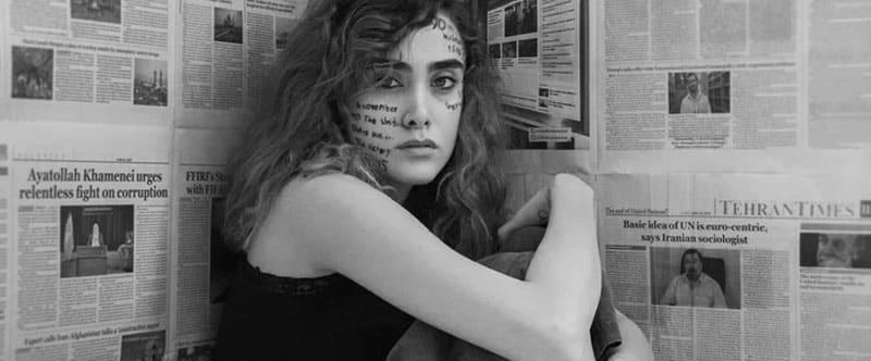 Jeune femme assise dans un coin, des mots écris sur le visage, des articles de journaux accrochés au mur