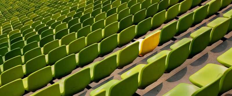 rangées de chaises vertes dans un stade, une seule chaise est jaune au milieu.