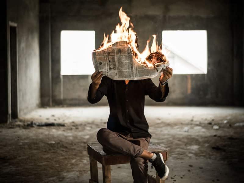Homme assis sur une chaise dans un bâtiment désaffecté en train de lire un journal qui brûle