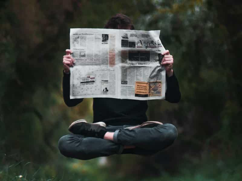 Homme en lévitation en train de lire des articles de journal, les pieds croisés en position du lotus
